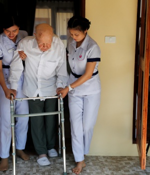 Wolfgang, 96, from Switzerland is helped to walk by two nurses, while staying at the Care Resort in Chiang Mai