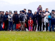 Migrants are escorted by German police after crossing the Austrian-German border in Wegscheid