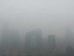Buildings are seen amid smog on a polluted day where a blue alert is issued, in Beijing