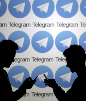 Two men pose with smartphones in front of a screen showing the Telegram logos in this picture illustration