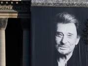 A giant poster of late French singer and actor Johnny Hallyday is displayed on the facade of the Madeleine Church during a 'popular tribute' in Paris