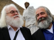 Two Karl Marx look-alike men, pose in front of a bronze statue of Marx in Trier