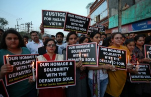 People hold candles and placards during a vigil, organised by the members of the Jammu and Kashmir High Court Bar Association, to show solidarity with the victim and demand a CBI probe into the rape and murder of an eight-year-old girl, in Jammu