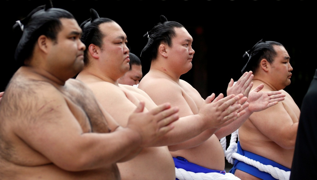 Sumo wrestlers pray during a ritual ceremony at the start of an annual sumo tournament dedicated at the Yasukuni Shrine in Tokyo