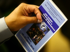 A priest holds a leaflet advertising a course for aspiring exorcists in Rome