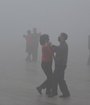 People wearing masks dance amid heavy smog during a polluted day at a square in Fuyang