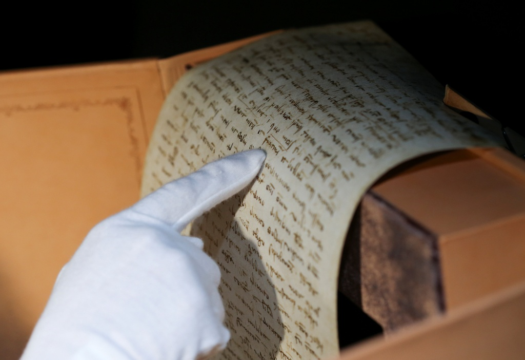 Rosi Fontana, spokeswoman for the Scrinium publishing house, points to an papyrus, part of the exact replica of Marco Polo's 700-year-old last will and testament, in Rome