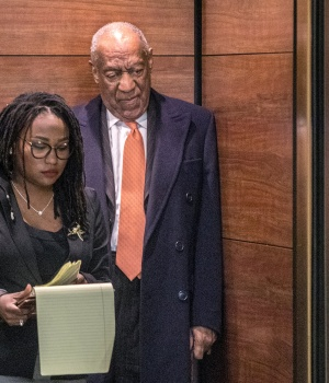 Bill Cosby stands with spokesperson Ebonee Benson as they wait for the elevator door to close at the end of his sexual assault retrial in Norristown