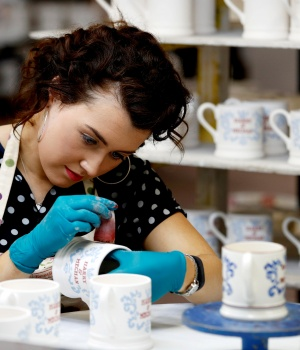 A worker prints a design onto a souvenir mug to commemorate the wedding of Britain's Prince Harry and Meghan Markle at the Emma Bridgewater Factory, in Hanley, Stoke-on-Trent