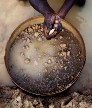 An artisanal miner pans for diamonds in the town of Koidu in eastern Sierra Leone