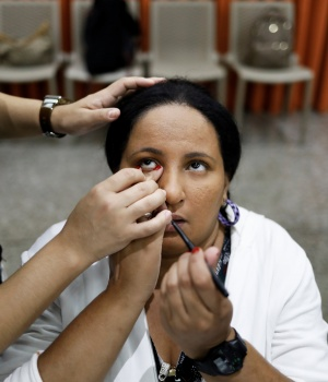 Flavia, who is visually impaired, gets make up put on by her teacher during a cosmetics class set up to help boost self-esteem at the Laramara association in Sao Paulo