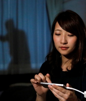 Leopalace 21 Corp employee, Mai Shibata, poses with her mobile phone during a demonstartion of the company's security system 'Man on the Curtain' in her room in Tokyo