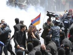 Law enforcement officers disperse the crowd during a protest against the appointment of ex-president Sarksyan as the new prime minister in Yerevan