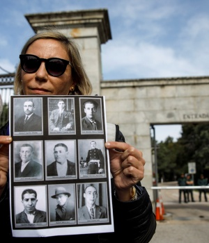 Silvia Navarro, a member of an organisation representing family members of civil war victims who have demanded to have their relatives exhumed, poses with a banner showing pictures of victims outside the entrance to the Basilica of the Valley of the Fallen