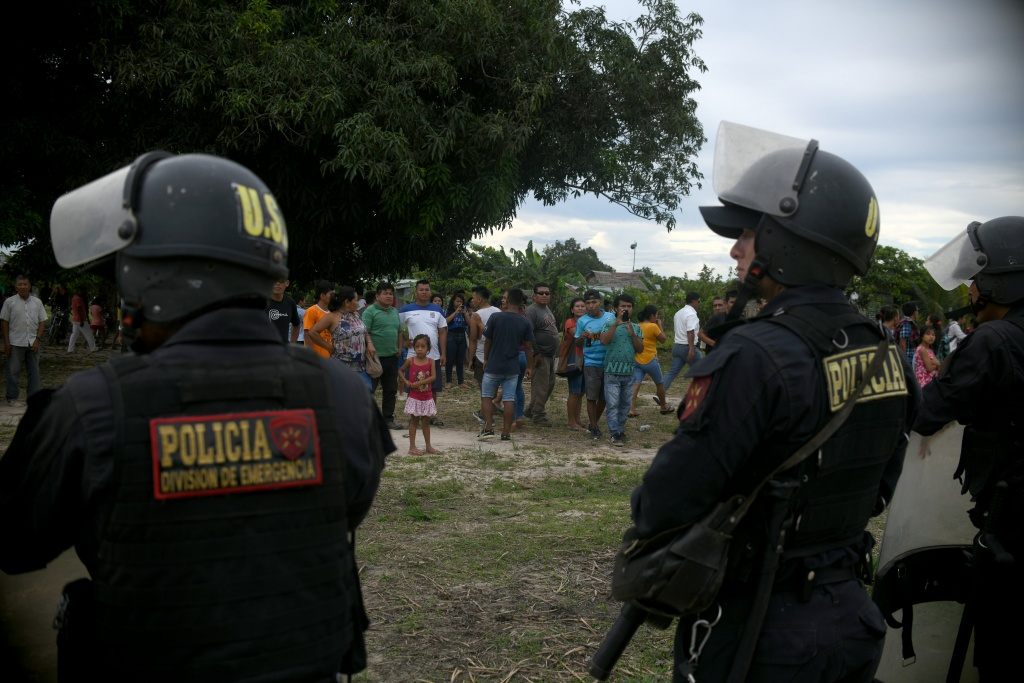 Police officers guard the funeral of Olivia Arevalo, in Pucallpa