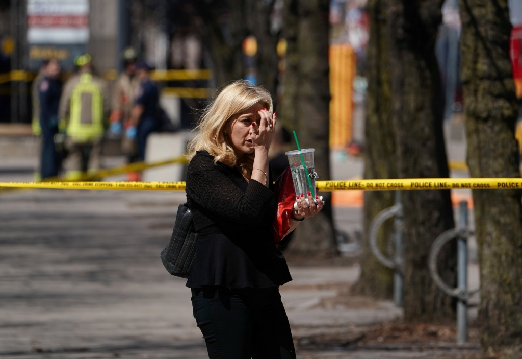 A pedestrian walks along a police crime scene tape near where a van struck multiple people at a major intersection in Toronto's northern suburbs in Toronto