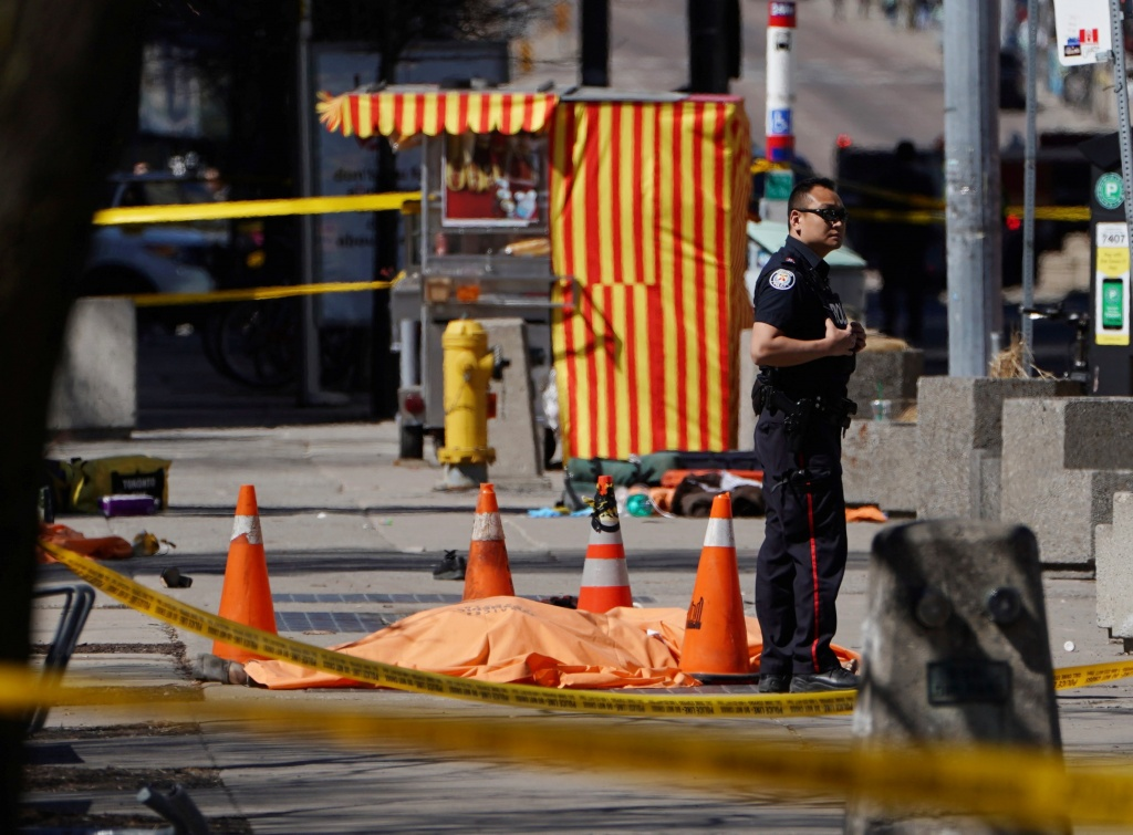 A police officer stands next to a victim of an incident where a van struck multiple people at a major intersection in Toronto's northern suburbs in Toronto