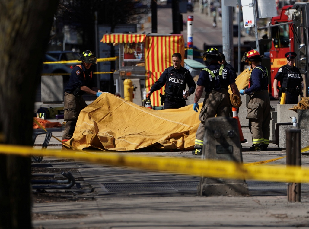 Firemen cover a victim of an incident where a van struck multiple people at a major intersection in Toronto's northern suburbs
