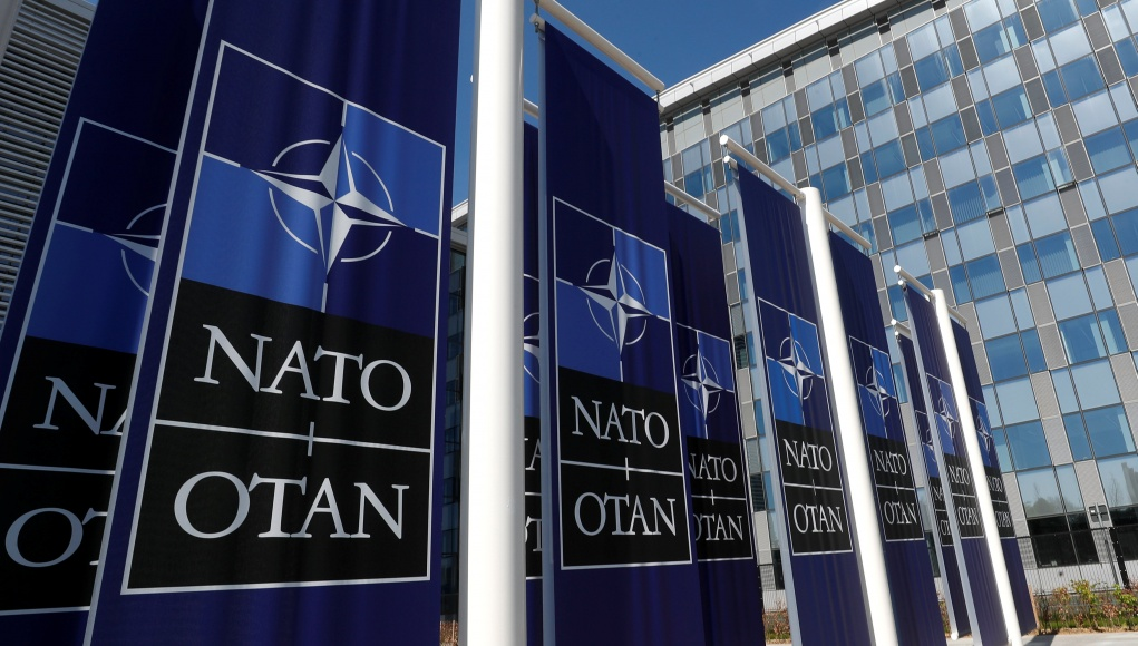 Banners displaying the NATO logo are placed at the entrance of new NATO headquarters during the move to the new building