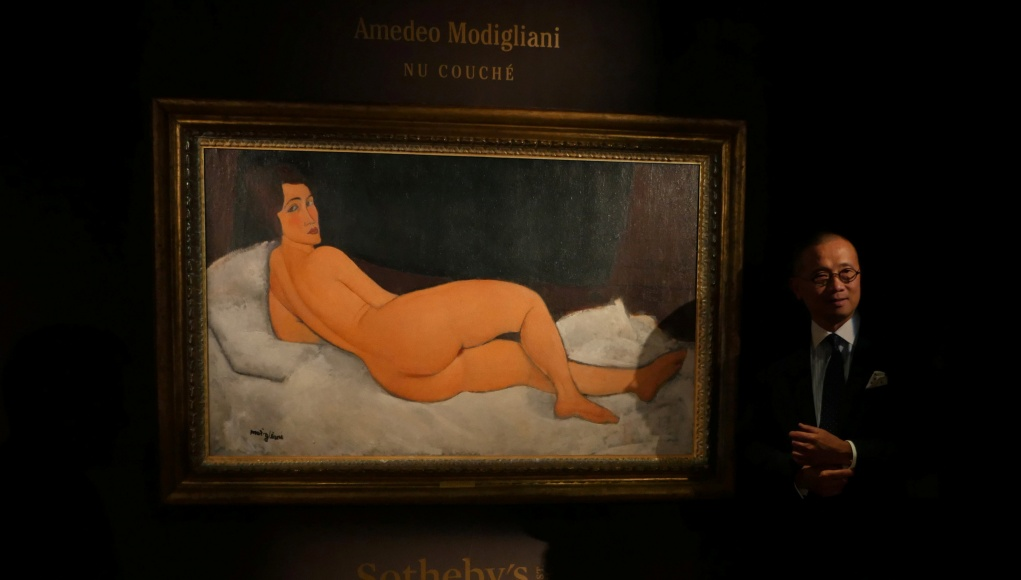 Kevin Ching, CEO of Sotheby's Asia, stands next to Amedeo Modigliani's