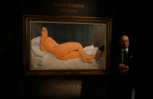 "Kevin Ching, CEO of Sotheby's Asia, stands next to Amedeo Modigliani's ""Nu couche"", expected to fetch over $150 million (USD) in the New York auction in May, during a preview in Hong Kong"