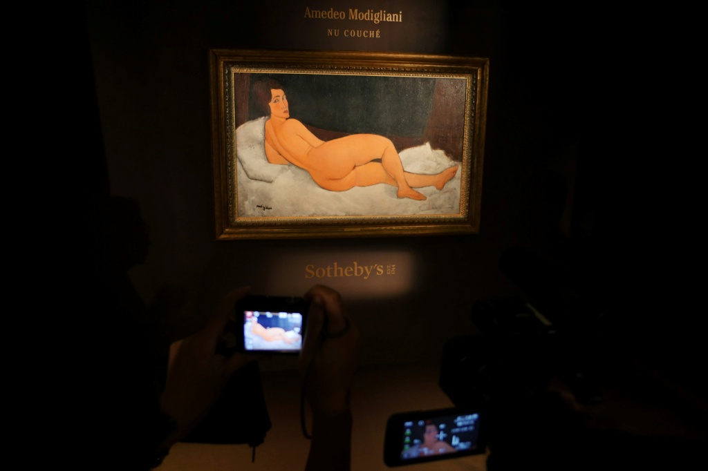 "Journalists take shots of Amedeo Modigliani's ""Nu couche"", expected to fetch over $150 million (USD) in the New York auction in May, during a preview in Hong Kong"