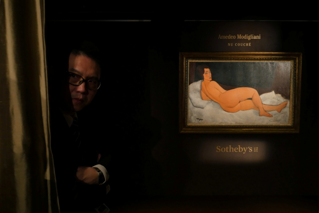"A security guard looks behind a curtain next to Amedeo Modigliani's ""Nu couche"", expected to fetch over $150 million (USD) in the New York auction in May, during a preview in Hong Kong"