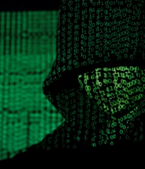 Projection of cyber code on hooded man is pictured in this illustration picture