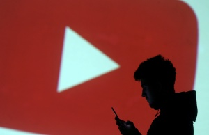 Silhouette of mobile user is seen next to a screen projection of Youtube logo in this picture illustration