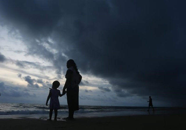 Mother holds her daughter's hand while they stand barefoot on a beach as rain clouds are seen over them in Colombo