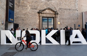A cyclist rides past a Nokia logo during the Mobile World Congress in Barcelona