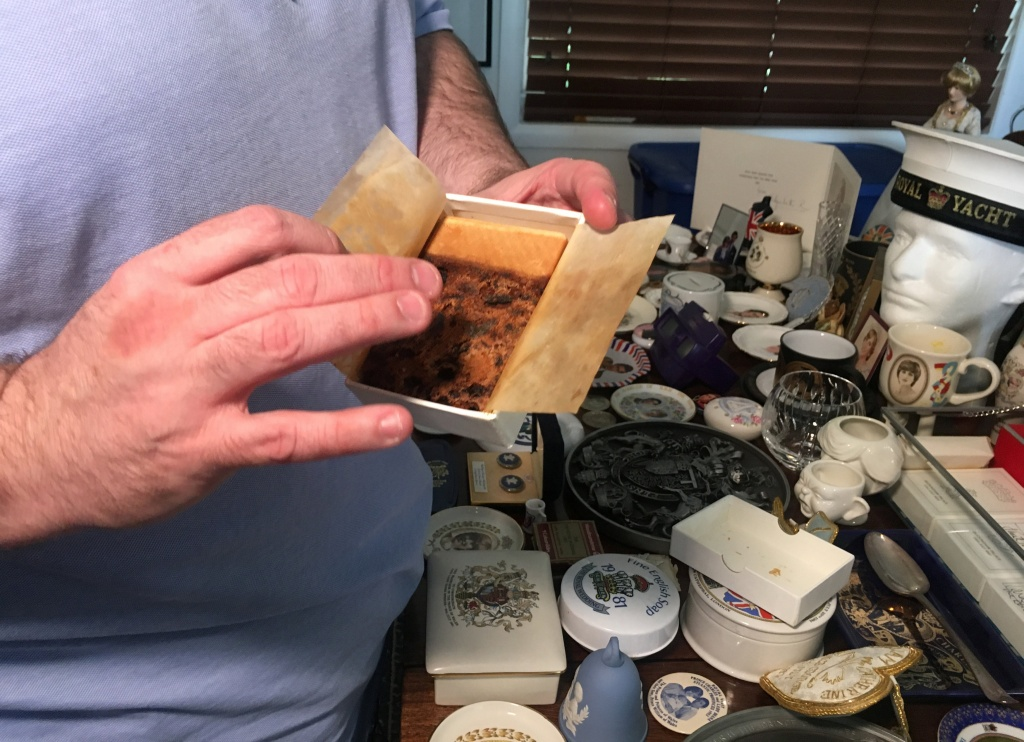 Collector John Hoatson shows a piece of wedding cake of Princess Diana from his collection of royal family memorabilia at his home in Pompano Beach