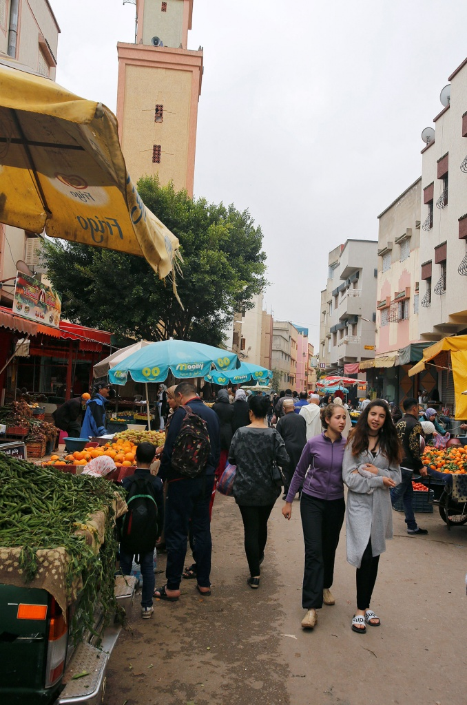 People walk past a fruits and vegetable stall at the market in Ouled Moussa district, on the outskirts of Rabat