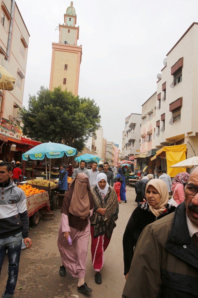 People walk past a fruit and vegetable stall at the market in Ouled Moussa district, on the outskirts of Rabat