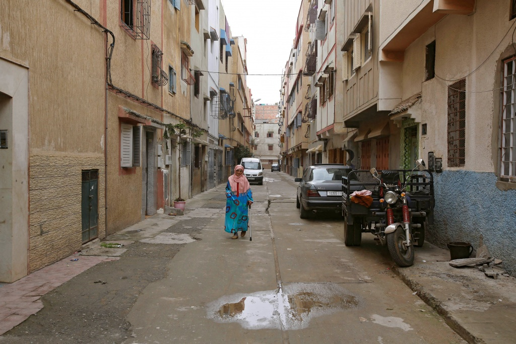 A woman walks along a narrow street in Ouled Moussa district, on the outskirts of Rabat