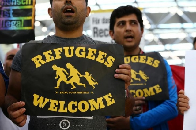 People protest against the German government's decision to deport migrants who were denied asylum, at Duesseldorf Airport