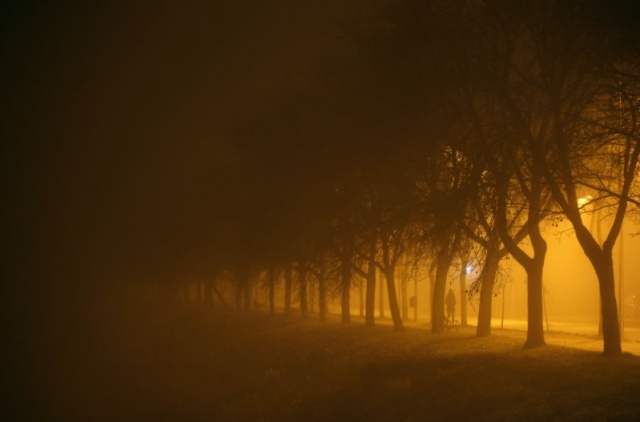 A woman walks along a street during heavy smog in the central Bosnian town of Zenica