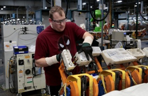 A General Motors assembly worker loads the HIC plastic caps at a Collaborative Robot adhesive station at Orion Assembly in Lake Orion,