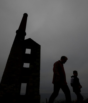 A family walk past the remains of the engine house at the Wheal Prosper copper and tin mine near Porthleven in Cornwall