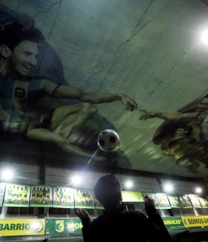 A boy plays soccer as images of Messi and Maradona are seen depicted on the ceiling in a recreation of Michelangelo's Sistine Chapel painting at Sportivo Pereyra club in Buenos Aires