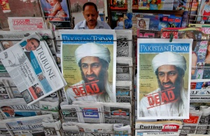 A roadside vendor sells newspapers with headlines about the death of al-Qaeda leader Osama bin Laden, in Lahore