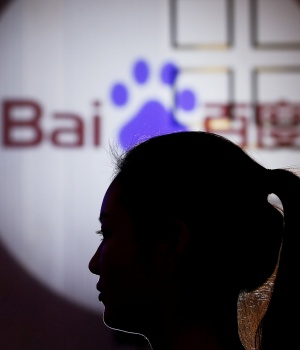 A woman is silhouetted against the Baidu logo at a new product launch from Baidu, in Shanghai, China
