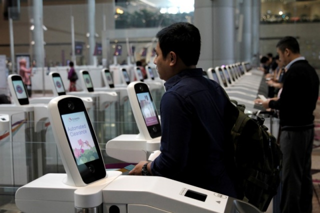 A passenger passes through an automated immigration control gate at Changi airport's Terminal 4 in Singapore