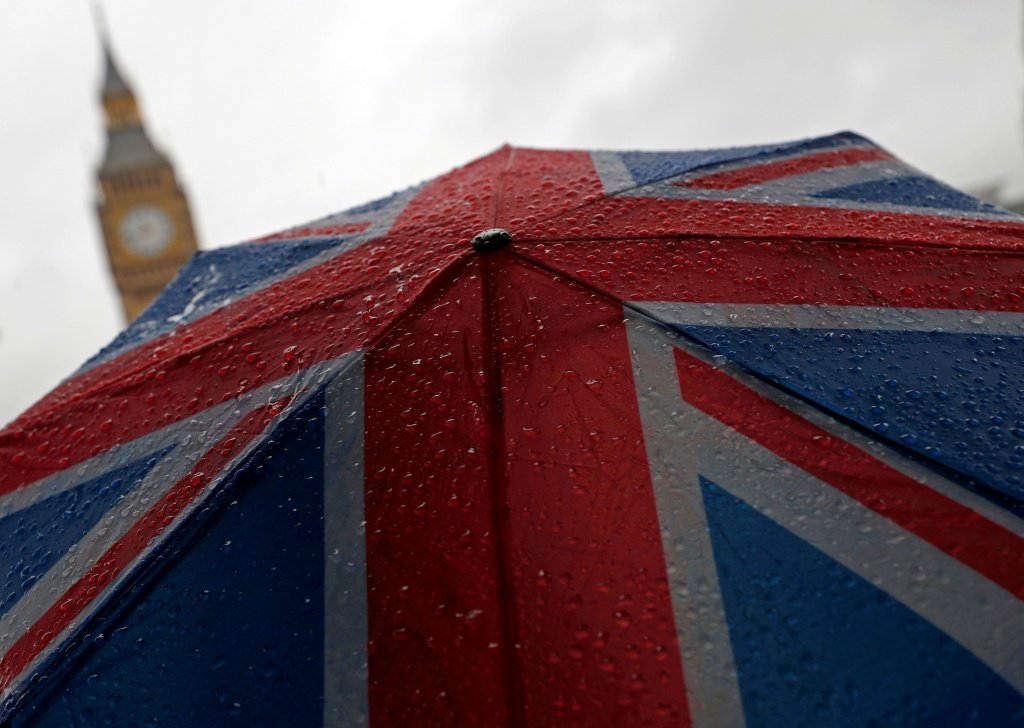 A Union Flag umbrella is seen in front of the Elizabeth Tower, commonly known as Big Ben, in London