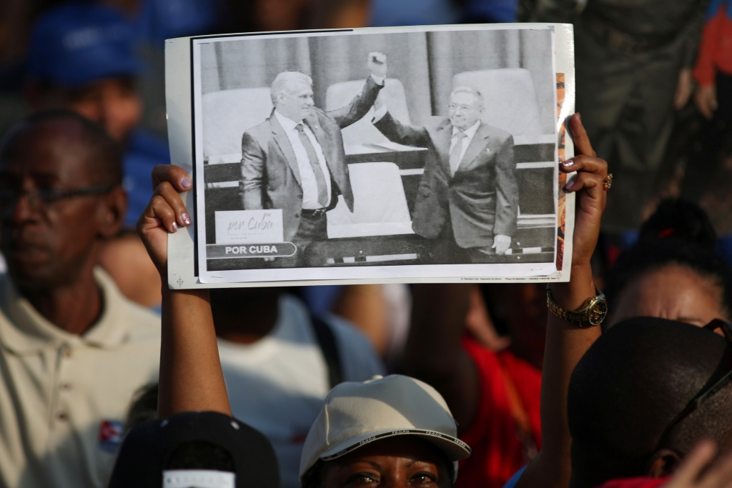 A woman carries an image of newly elected Cuban President Miguel Diaz-Canel as former Cuban President Raul Castro raises his hand, during the May Day rally in Havana