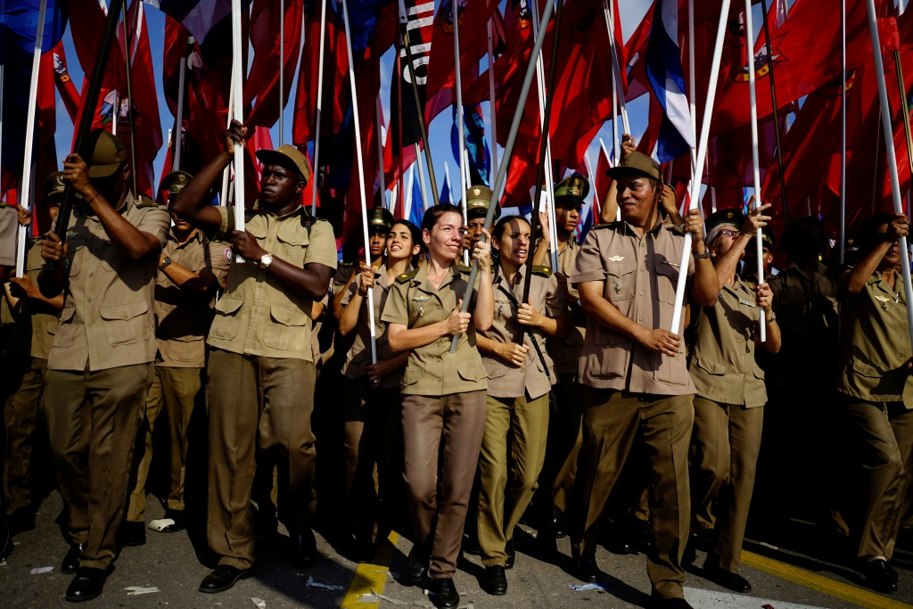 Army soldiers carry flags during the May Day rally in Havana