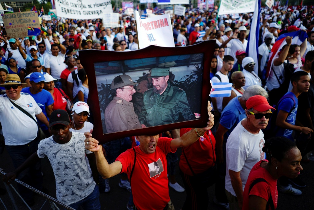 A man shouts slogans as he carries an image of Cuba's First Secretary of the Communist Party and former President Raul Castro and Cuba's late President Fidel Castro during the May Day rally in Havana