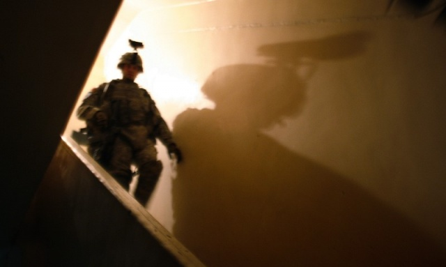 U.S. soldier's night vision goggles casts a shadow during a search for criminals and weapons in Baghdad's Mansour district