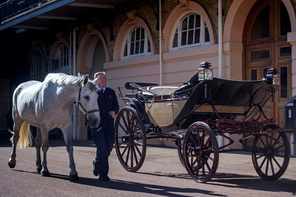 Philip Barnard-Brown, Senior Coachman at the Buckingham Palace Mews, leads a Windsor Grey, one of the four horses that will pull the carriage at the wedding of Prince Harry and Meghan Markle, past the Ascot Landau carriage, at the Royal Mews at Buckingham