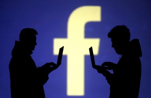 Silhouettes of laptop users are seen next to a screen projection of Facebook logo in this picture illustration